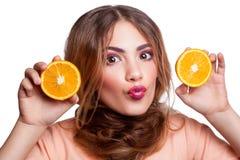 Muchacha divertida hermosa joven con la rebanada y el maquillaje anaranjados y peinado que mira la cámara Imagenes de archivo