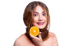 Muchacha divertida hermosa joven con la rebanada y el maquillaje anaranjados y peinado que mira la cámara Foto de archivo