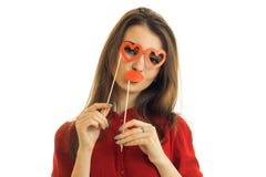 Muchacha divertida joven con los labios y los vidrios de papel en la forma del corazón Fotos de archivo libres de regalías
