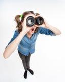 Muchacha divertida linda con dos colas de potro que miran a través de las lentes de la foto granangulares Fotografía de archivo