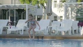 Muchacha divertida linda con dos coletas en el traje de natación que salta en la piscina y que salpica la diversión en el agua Ni almacen de metraje de vídeo
