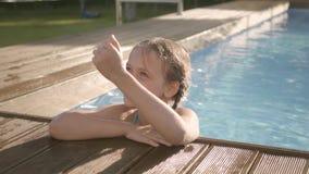 Muchacha divertida linda con la risa de las coletas, mostrando el pulgar encima de la mirada fuera de la piscina, aferrándose al  almacen de video