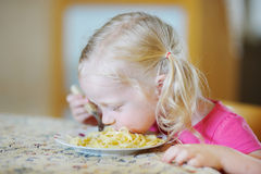 Muchacha divertida linda que come los espaguetis Imagen de archivo