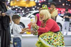 Muchacha divertida no identificada que hace feliz childern en la expo internacional 2015 del motor de Tailandia Fotografía de archivo libre de regalías
