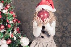 Muchacha divertida que adorna un árbol de navidad Fotos de archivo