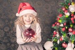 Muchacha divertida que adorna un árbol de navidad Imagen de archivo libre de regalías