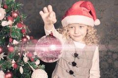 Muchacha divertida que adorna un árbol de navidad y que sostiene la bola Imágenes de archivo libres de regalías