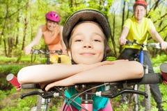 Muchacha divertida que apoya contra el manillar de la bici Imágenes de archivo libres de regalías