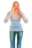 Muchacha divertida que grita a través de las manos formadas megáfono Foto de archivo