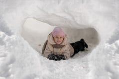 Muchacha divertida que juega en un iglú de la nieve en un día de invierno soleado Fotos de archivo libres de regalías