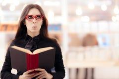 Muchacha divertida que lee un libro delante de un estante Foto de archivo libre de regalías
