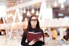 Muchacha divertida que lee un libro delante de un estante Imagen de archivo libre de regalías