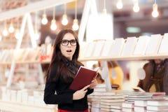 Muchacha divertida que lee un libro delante de un estante Imagenes de archivo