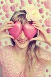 Muchacha divertida que lleva a cabo corazones en estilo del ojo-vintage Imagen de archivo