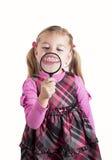 Muchacha divertida que muestra los dientes con magnificar Imagenes de archivo