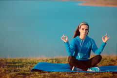 Muchacha divertida que reflexiona sobre la estera de la yoga en naturaleza Fotos de archivo
