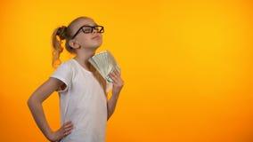 Muchacha divertida que se aviva con el manojo de dólares, primera renta, lotería que gana almacen de video