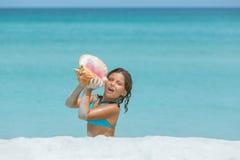 Muchacha divertida que se sienta en la playa blanca de la arena que se considera grande Foto de archivo