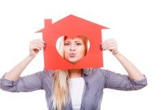 Muchacha divertida que sostiene la casa de papel roja con forma del corazón Fotos de archivo libres de regalías
