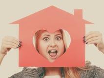 Muchacha divertida que sostiene la casa de papel roja con forma del corazón Foto de archivo libre de regalías