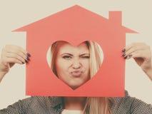 Muchacha divertida que sostiene la casa de papel roja con forma del corazón Imagen de archivo libre de regalías