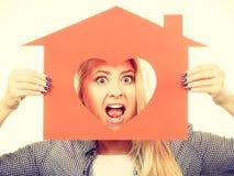 Muchacha divertida que sostiene la casa de papel roja con forma del corazón Imagen de archivo