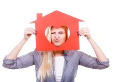 Muchacha divertida que sostiene la casa de papel roja con forma del corazón Fotografía de archivo libre de regalías