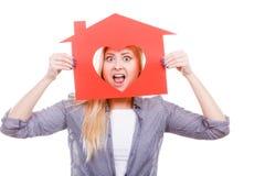 Muchacha divertida que sostiene la casa de papel roja con forma del corazón Foto de archivo