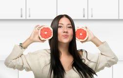 Muchacha divertida que sostiene la fruta cítrica en la cocina Imagenes de archivo