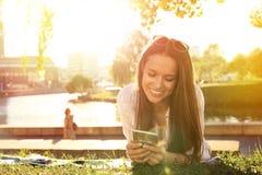 Muchacha divertida que usa un smartphone en la hierba de un parque con un fondo verde Imagen de archivo libre de regalías
