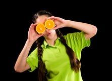 Muchacha divertida sorprendida con la naranja cortada en ojos Imágenes de archivo libres de regalías
