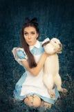 Muchacha divertida vestida como Alicia en el país de las maravillas con el conejo blanco Imagen de archivo