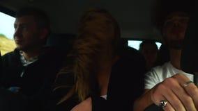 Muchacha divertida y su baile del amigo al musik como loco en coche grande cerca de otras personas que conducen a las vacaciones  almacen de video