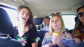Muchacha divertida y su baile del amigo al musik como loco en coche grande cerca de otras personas que conducen a las vacaciones  metrajes