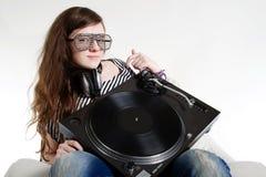Muchacha DJ que se sienta con la placa giratoria en sus brazos Fotografía de archivo