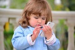 Muchacha dos años, con un teléfono celular en el parque Imagen de archivo