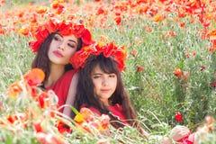 Muchacha dos con la guirnalda de las flores de las amapolas Foto de archivo