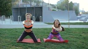 Muchacha dos que hace ejercicio activo con sonrisa en la hierba por la mañana en 4K metrajes