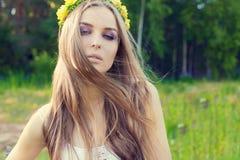 Muchacha dulce atractiva hermosa con el pelo largo y una guirnalda de rosas amarillas en su cabeza en el campo, el viento que sop Foto de archivo libre de regalías