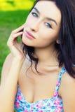 Muchacha dulce atractiva joven hermosa con los ojos azules con el pelo negro largo que se sienta en el parque en un día de verano Foto de archivo libre de regalías