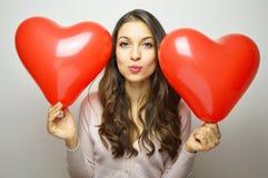 Muchacha dulce con los globos del corazón de la tarjeta del día de San Valentín que miran la cámara y que hacen beso del aire Imágenes de archivo libres de regalías