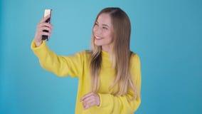 Muchacha dulce con un teléfono que habla en una llamada video en el smartphone, mirando la pantalla del teléfono con la cara asom almacen de video