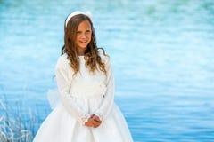Muchacha dulce en el vestido blanco de la comunión. Fotografía de archivo
