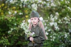 Muchacha dulce en un uniforme militar con un ramo de flor de la manzana Imágenes de archivo libres de regalías