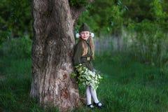 Muchacha dulce en un uniforme militar con un ramo de flor de la manzana Fotos de archivo libres de regalías
