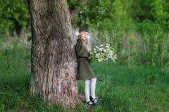 Muchacha dulce en un uniforme militar con un ramo de flor de la manzana Imagen de archivo