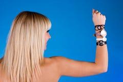 Muchacha dulce hermosa con diverso reloj en la mano Foto de archivo libre de regalías