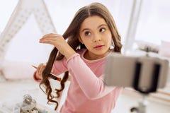 Muchacha dulce que cepilla su pelo y que lo filma Fotos de archivo