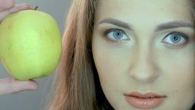 Muchacha dulce que come la manzana verde en fondo gris metrajes
