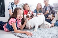 Muchacha dulce que juega con los perritos del dogo en el cuarto de niños Fotos de archivo libres de regalías